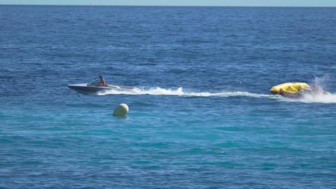Happy people enjoying banana boat ride, cool attraction at sea resort, summer Footage