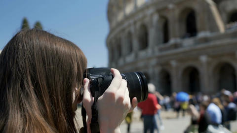 Young woman taking picture of Colosseum on camera, enjoying hobby on vacation Live Action