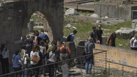Slow-mo of tourist group entering archeological site to view historical ruins Footage