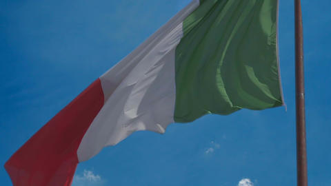 Patriotic Italian flag flying in wind against blue sky background, slow motion Footage