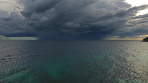 Flying over sea to thunderstorm on horizon Live Action