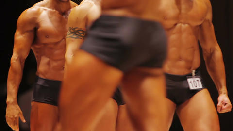 Male bodybuilders walking on stage to show strong muscular bodies at contest Live Action