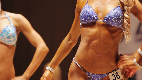 Women bodybuilders changing relaxed poses to show ideal toned bodies at contest Live Action