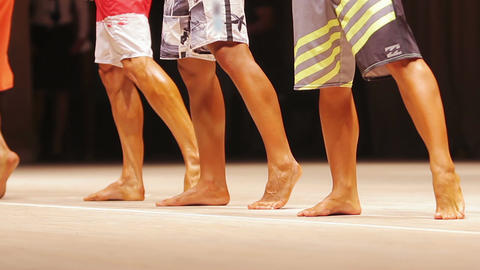 Feet of male fitness models lined up on stage, posing at bodybuilding contest Live Action