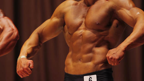 Perfect masculine torso of strong bodybuilder showing muscles at fitness contest Footage