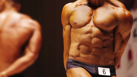 Muscular contestant standing in side triceps pose at bodybuilding competition Footage