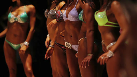 Fit ladies showing perfect tanned bodies in relaxed poses at fitness competition Live Action