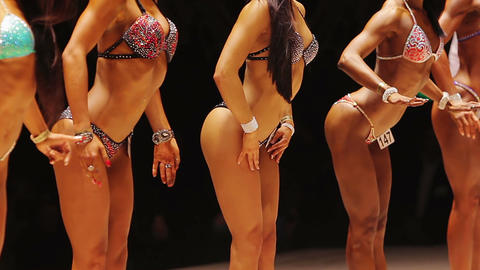 Strained female bodybuilders posing on stage in bikini, fitness competition Live Action