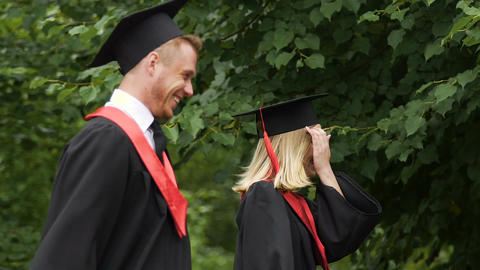 Young man and woman celebrating university graduation with happy smiles on faces Footage