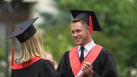 Happy students exchanging congratulations, hugging warmly, graduation ceremony Footage