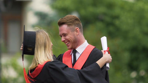 Excited male and female university graduates exchanging congratulations, hugging Footage