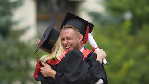 Best friends hugging warmly and laughing, celebrating graduation from university Footage