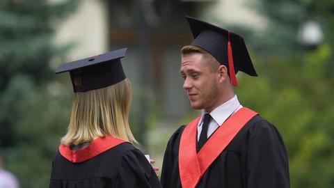 Male and female graduates in academic caps hugging, friends sorry to say goodbye Footage