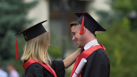 Male and female friends hugging, holding higher education diplomas in hands Footage