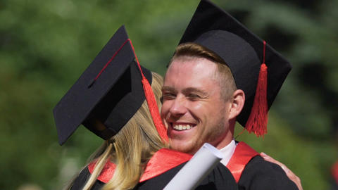 Successful graduating students hugging and laughing cheerfully, friendship Footage