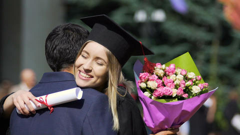 Happy female embracing warmly man with bunch of flowers, graduation ceremony Footage