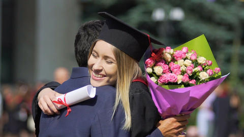 Happy female graduate receiving congratulations and flowers from boyfriend Footage
