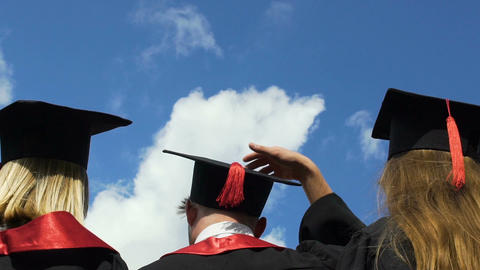 Happy young people celebrating graduation, throwing academic hats up in air Footage