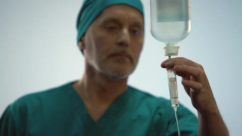Male doctor checking intravenous therapy drip, taking care of patient, medicine Footage