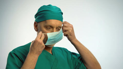 Male doctor putting on face mask to examine patient, protection against disease Footage