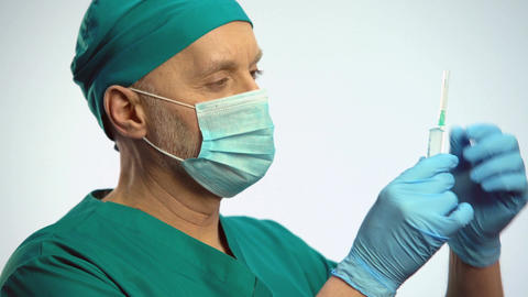 Doctor in face mask nodding and taking syringe, preparing to make injection Footage