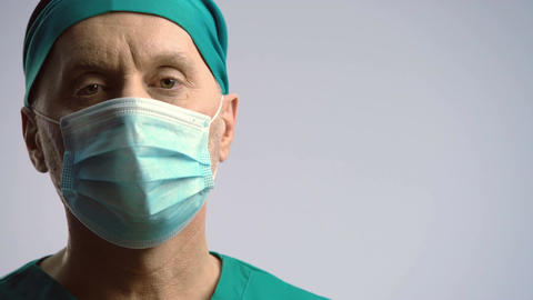 Serious face of surgeon in medical face mask looking to camera, health insurance Footage