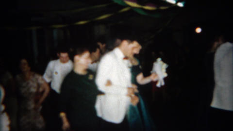 1966: Crowd following wedding couple around reception hall Footage