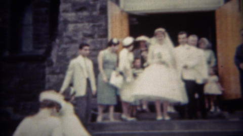 1956: Newlywed couple leaving church steps rice tossed Footage