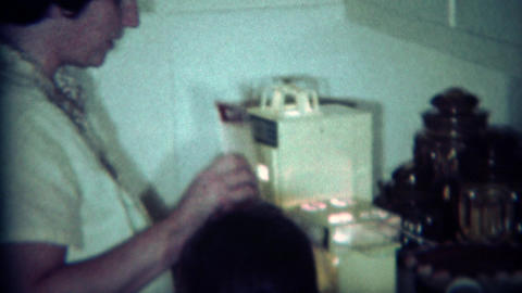 1970: Girl cooks with Easy Bake Oven with mother supervision Footage