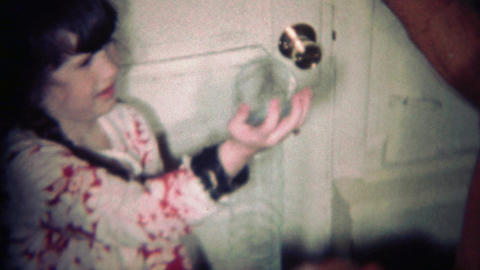 1970: Brother teaches sister how a metal slinky toy works Footage