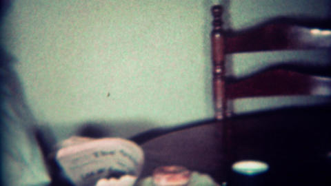 1970: Dad reads newspaper morning coffee on kitchen table Footage