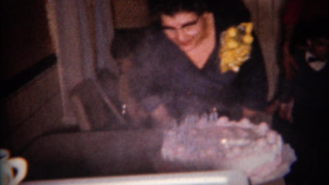 1959: Lady blows out birthday cake with many smoking candles Footage