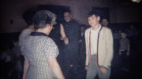 1966: Teenager dances with grandma around smoke filled reception hall Footage