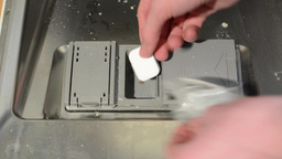 insert detergent tablet to the dishwasher (opening for tablet) Footage