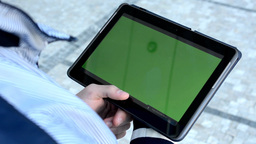 Man looks at the tablet (green screen) on the street Footage
