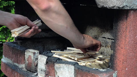 Man arranges wood oven grill to give them fire and prepare the food Footage