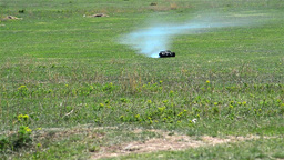 Toy car travels fast on a green grass pasture with white smoke leaving behind he Footage