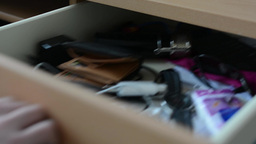 Hand opens and closes the drawer with different things (close up) Footage