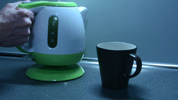 Switching on the kettle and Insert a tea bag into a cup to on the kitchen counte Footage