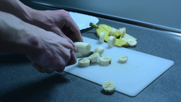 Cutting a banana into slices and inserting on the plate on the kitchen counter Footage
