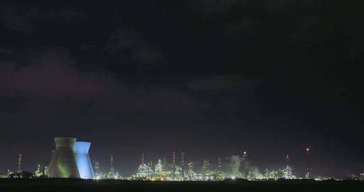 Night footage of a large oil refinery with smokestacks and steam rising Footage