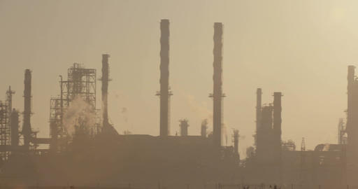 Sunrise over a large oil refinery with smoke rising Footage