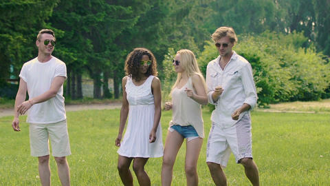 Flirty beautiful ladies and smiling handsome men dancing outdoors in summer Footage