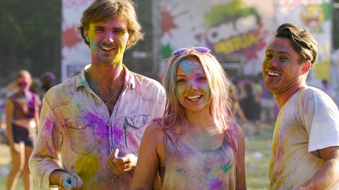 Beautiful blonde female throwing handful of color powder in air, enjoying life Footage