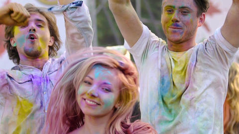 Active young people dancing and looking to camera, having fun at color festival Footage