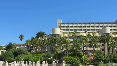 Contemporary hotel decorated with palms near the ocean, luxury vacation resort Live Action