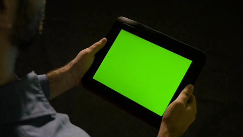 A business man holds green screen tablet pc in hand and fast swiping on the disp Footage