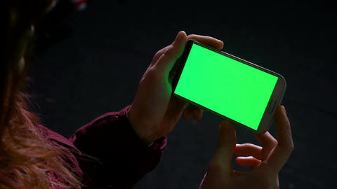Hands of woman holding a smart phone with green screen and swiping Footage