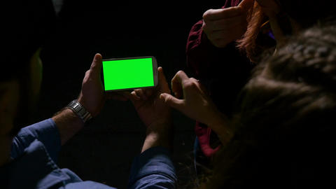 Group of teen laughing and having fun while watching a green screen smart phone Footage