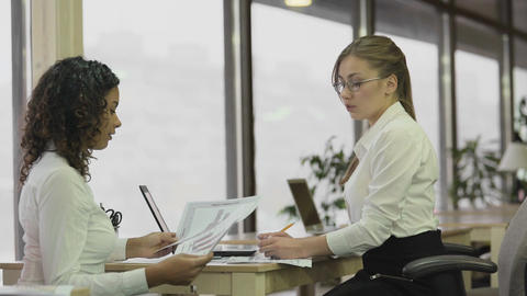 Strict female team leader checking papers with employee, brainstorming project Live Action